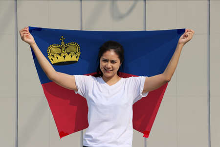 pretty lady is holding Liechtenstein flag in her hands and raising to the end of the arm at the back on grey background. Imagens