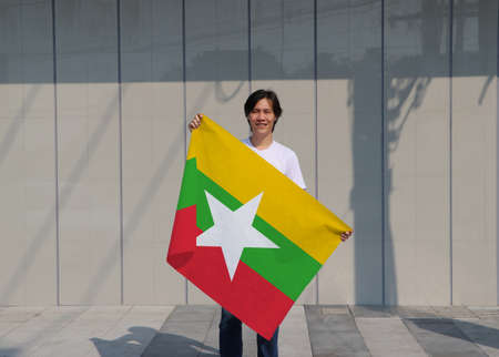 The man is holding Myanmar flag in his hands on grey background.