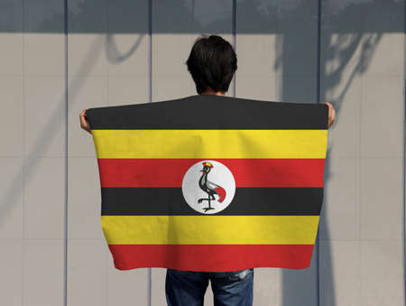 The man is holding Uganda flag on his shoulder and turn back on grey background. Imagens
