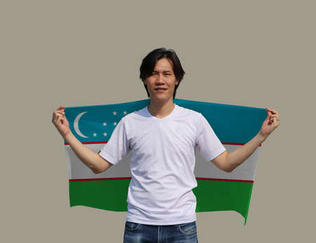 The man is holding Uzbekistan fabric flag on his shoulder on grey background. Imagens