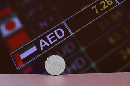 The coin of United Arab Emirates one dirham money on obverse on brown floor with digital board of currency exchange money background. Concept of finance or currency.