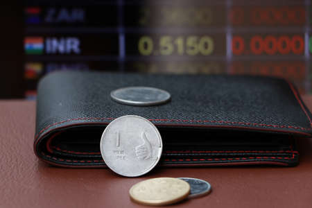 The coin of India Rupee money and black leather wallet on brown floor with digital board of currency exchange background. Concept of finance.