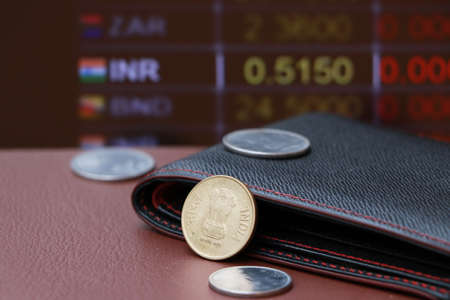 The brass coin of India Rupee money and black leather wallet on brown floor with digital board of currency exchange background. Concept of finance. Imagens