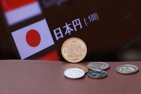 The copper coin of Japanese Yen money and the coins on brown floor with digital board of currency exchange background. Concept of finance.