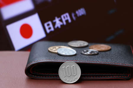 The coin of one hundred Japanese Yen money and the coins on black leather wallet on brown floor with digital board of currency exchange background. Concept of finance. Imagens
