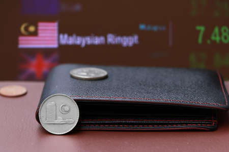 Twenty cents coin of Malaysia Ringgit money and the coins on black leather wallet and brown floor with digital board of currency exchange background. Concept of finance.
