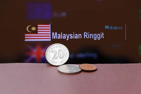 Twenty cents coin of Malaysia Ringgit money and the coins on brown floor with digital board of currency exchange background. Concept of finance.