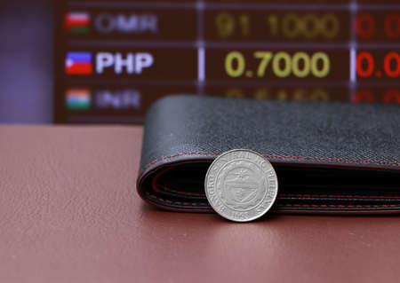 The coin of Philippine peso money and black leather wallet on brown floor with digital board of currency exchange money background. Concept of finance or currency.