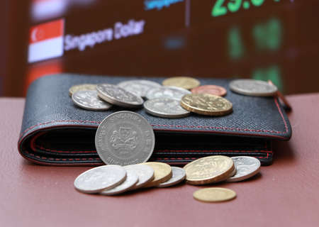 The heap coins of Singapore dollar money and black leather wallet on brown floor with digital board of currency exchange money background. Concept of finance or currency.