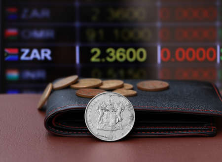 The heap coins of South Africa Rand money and black leather wallet on brown floor with digital board of currency exchange money background. Concept of finance or currency.