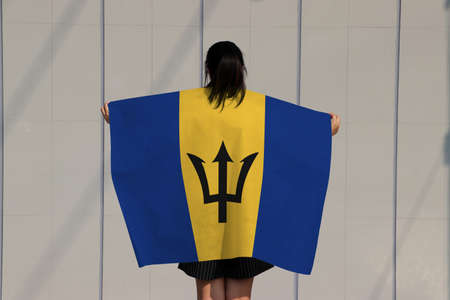 Woman is holding Barbados flag on her shoulder and turn back on grey background.