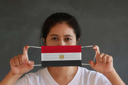 A woman in white shirt with Egypt flag on hygienic mask in her hand and lifted up the front face on dark grey background. Tiny Particle or virus corona or Covid 19 protection. Concept of Combating illness.