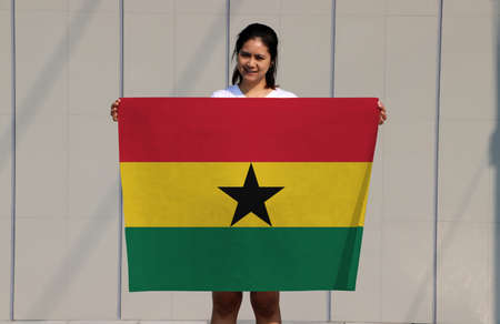 pretty lady is holding Ghana flag in her hands on grey background.