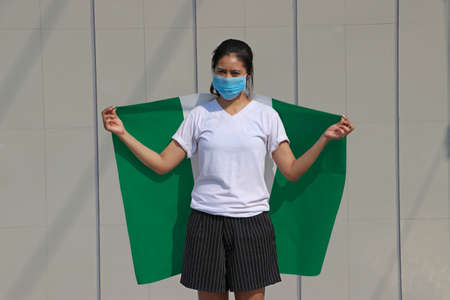 Masked woman prevent germs and holding Nigeria fabric flag on her shoulder on grey background. Tiny Particle or virus corona or Covid 19 protection.