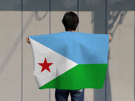 The man is holding Djibouti flag on his shoulder and turn back on grey background.