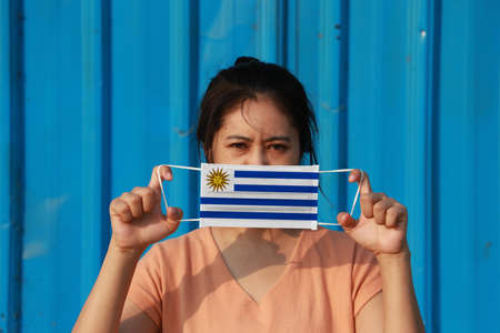 A woman with Uruguay flag on hygienic mask in her hand and lifted up the front face on blue background. Tiny Particle or virus corona or Covid 19 protection. Concept of Combating illness.