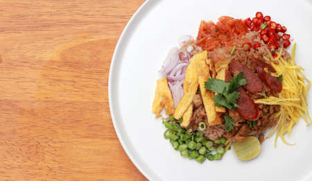 Shrimp Paste Rice Salad in the white round plate on the wooden floor.