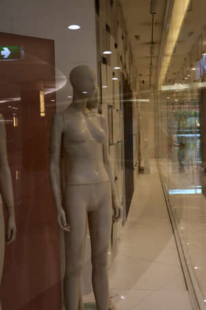 Mannequins for clothes but have not yet brought clothes to decorate located in a glass showroom.