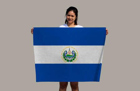 pretty lady is holding El Salvador flag in her hands on grey background. Reklamní fotografie