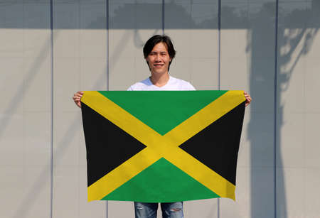 The man is holding Jamaica flag in his hands on grey background.