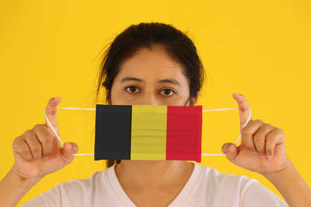 A woman in white shirt with Belgium flag on hygienic mask in her hand and lifted up the front face on yellow background. Tiny Particle or virus corona or Covid 19 protection. Concept of Combating illness.