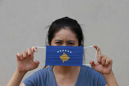 A woman with Kosovo flag on hygienic mask in her hand and lifted up the front face on beige color background. Tiny Particle or virus corona or Covid 19 protection. Concept of Combating illness. Reklamní fotografie