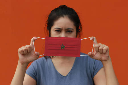 A woman with Morocco flag on hygienic mask in her hand and lifted up the front face on orange color background. Tiny Particle or virus corona or Covid 19 protection. Concept of Combating illness.