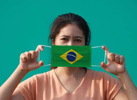 A woman with Brazil flag on hygienic mask in her hand and lifted up the front face on green background.  Concept of Combating illness.
