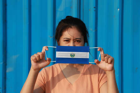A woman with El Salvador flag on hygienic mask in her hand and lifted up the front face on blue background. Concept of Combating illness.