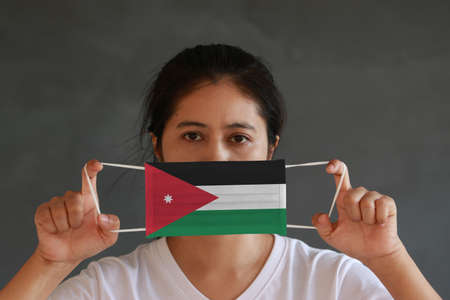 A woman with Jordan flag on hygienic mask in her hand and lifted up the front face on dark green background.  Concept of Combating illness.