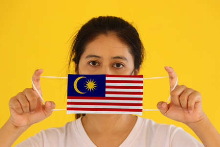 A woman in white shirt with Malaysia flag on hygienic mask in her hand and lifted up the front face on yellow background. Concept of Combating illness.