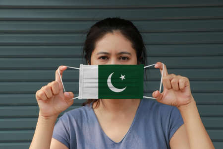 A woman with Pakistan flag on hygienic mask in her hand and lifted up the front face on dark green background. Concept of Combating illness.