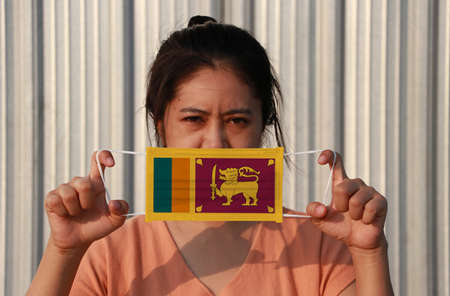 A woman with Sri Lanka flag on hygienic mask in her hand and lifted up the front face on grey background.  Concept of Combating illness. 版權商用圖片