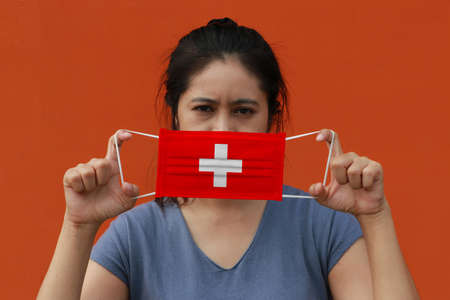 A woman with Switzerland flag on hygienic mask in her hand and lifted up the front face on orange color background. Concept of Combating illness. 版權商用圖片