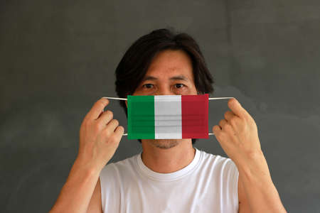 A man with Italy flag on hygienic mask in his hand and lifted up the front face on yellow background. Concept of Combating illness.