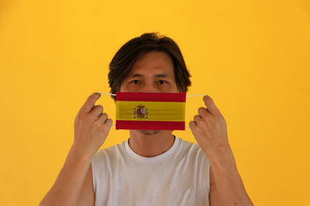 A man with Spain flag on hygienic mask in his hand and lifted up the front face on yellow background. Concept of Combating illness.