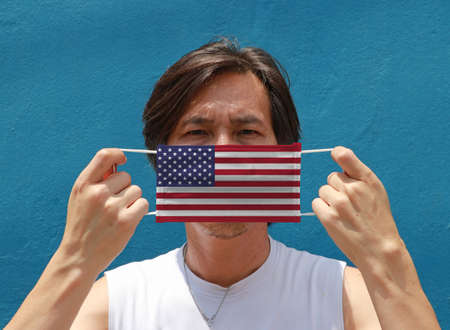 A man with America on hygienic mask in his hand and lifted up the front face on blue background. Concept of Combating illness.