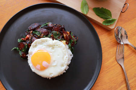 Chinese sausage fried with basil and fried egg with rice in the black round dish, Cooking ingredients with spoon and fork on the wooden floor.