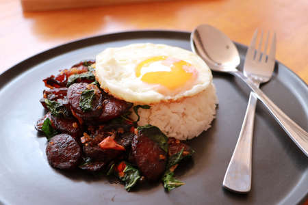 Chinese sausage fried with basil and fried egg with rice in the black round dish, with spoon and fork on the wooden floor.