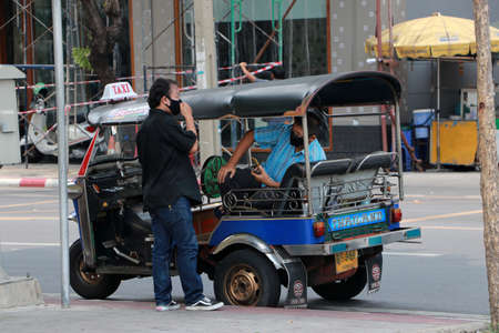 Bangkok, Thailand - 29 May, 2020 : Tuk Tuk driver talking to passenger and everybody wear hygienic mask  to prevent Covid 19.