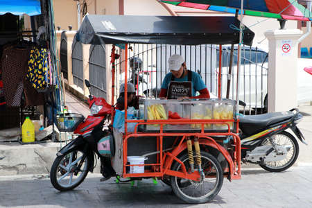 Pathumthani, Thailand - 29 May, 2020 : Fruit street vendor in the side wheeled tricycle beside road.
