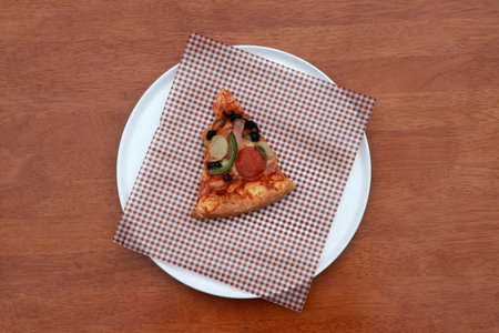 A piece of triangle Pizza  place on brown scotch paper  in the white round plate on the wooden floor.