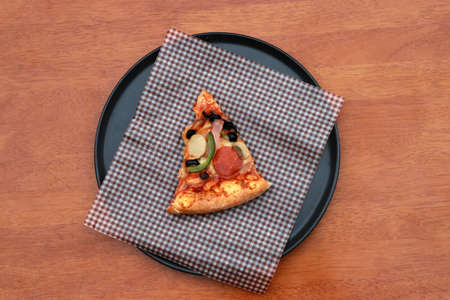 A piece of triangle Pizza  place on brown scotch paper  in the black round plate on the wooden floor.