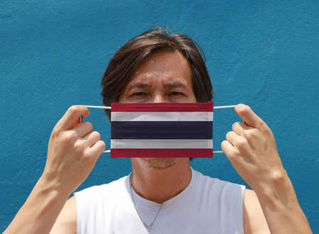 A man with Thailand flag on hygienic mask in his hand and lifted up the front face on blue background. Tiny Particle or virus corona or Covid 19 protection. Concept of Combating illness.