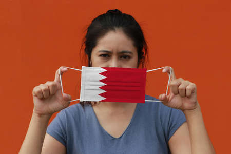 A woman with Bahrain flag on hygienic mask in her hand and lifted up the front face on orange color background. Tiny Particle or virus corona or Covid 19 protection. Concept of Combating illness. 版權商用圖片