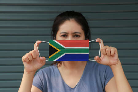 A woman with South Africa flag on hygienic mask in her hand and lifted up the front face on dark green background. Tiny Particle or virus corona or Covid 19 protection. Concept of Combating illness. 版權商用圖片