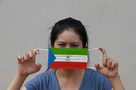 A woman with Equatorial guinea flag on hygienic mask in her hand and lifted up the front face on beige color background. Tiny Particle or virus corona or Covid 19 protection. Concept of Combating illness.