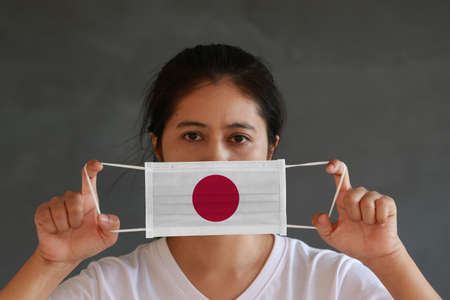 A woman in white shirt with Japan flag on hygienic mask in her hand and lifted up the front face on dark grey background. Tiny Particle or virus corona or Covid 19 protection. Concept of Combating illness.