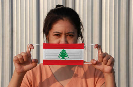 A woman with Lebanon flag on hygienic mask in her hand and lifted up the front face on grey background. Tiny Particle or virus corona or Covid 19 protection. Concept of Combating illness.