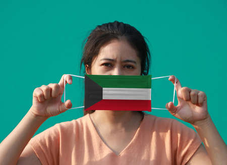 A woman with Kuwait flag on hygienic mask in her hand and lifted up the front face on green background. Tiny Particle or virus corona or Covid 19 protection. Concept of Combating illness. 版權商用圖片